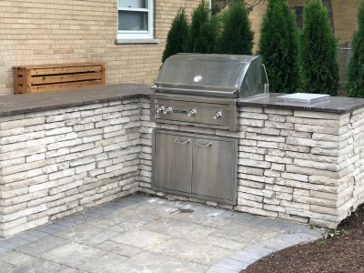 Custom built BBQ grill and counter top using Rivercrest Wall by Unilock Outdoor Kitchen